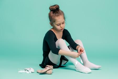 pies bonitos: pequeña bailarina hermosa en el vestido negro para bailar que pone en zapatillas de punta del pie