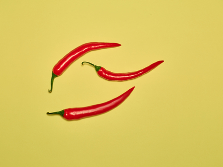 bitter chili pepper and paprika on a yellow background Stock Photo