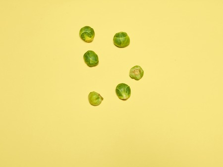 The piles of Brussels sprouts on a yellow background