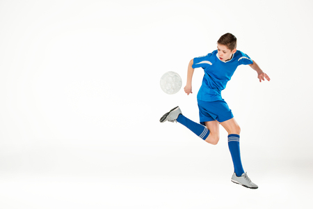 white: Young boy with soccer ball doing flying kick