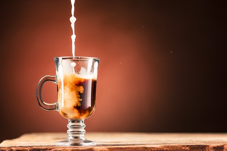 adding: Adding milk to a cup of coffee.