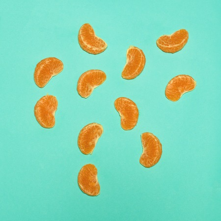 Ripe Mandarin fruits peeled open on the blue background