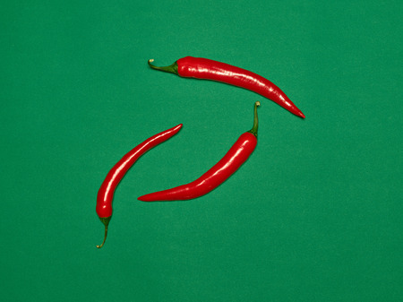 bitter chili pepper and paprika on a green background