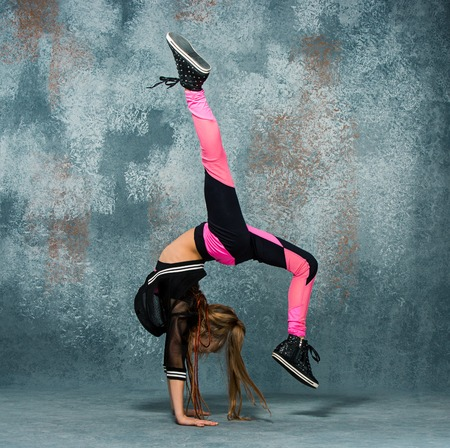 Young girl break dancing on wall background. Stock Photo