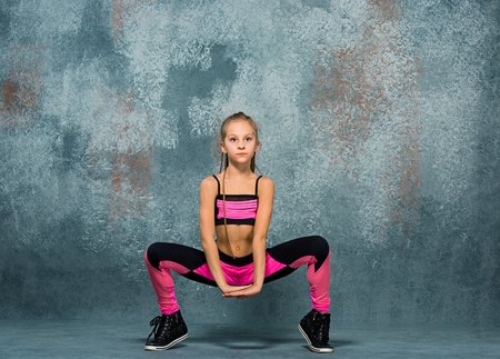Young girl break dancing on wall background. Stock Photo