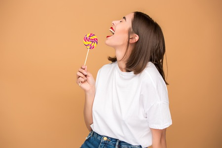The young woman with colorful lollipop