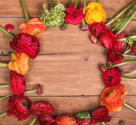 Ranunkulyus bouquet of red flowers on a wooden background Stock Photo