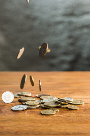 Die silbernen und goldenen Münzen und fallenden Münzen auf Holzuntergrund Standard-Bild - 74378644