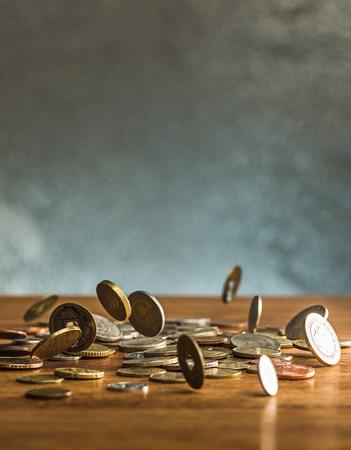 Die silbernen und goldenen Münzen und fallenden Münzen auf Holzuntergrund Standard-Bild - 74378483