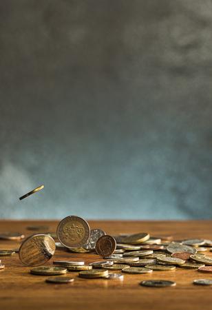 Die silbernen und goldenen Münzen und fallenden Münzen auf Holzuntergrund Standard-Bild - 74378482