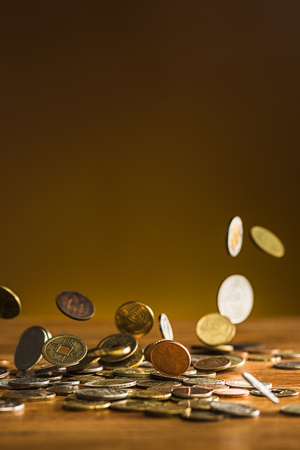 The silver and golden coins and falling coins on wooden background Standard-Bild