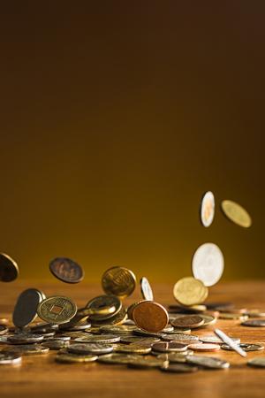 Die silbernen und goldenen Münzen und fallenden Münzen auf Holzuntergrund Standard-Bild - 74378487