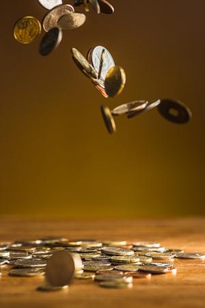 Die silbernen und goldenen Münzen und fallende Münzen auf Holzuntergrund Standard-Bild - 74378488