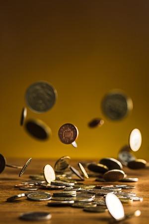 Die silbernen und goldenen Münzen und fallenden Münzen auf Holzuntergrund Standard-Bild - 74378496