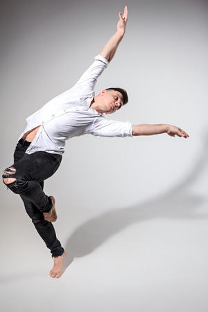 The young man dancing on gray Stock Photo