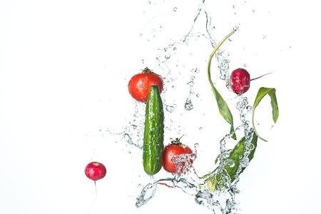 De verse tomaten, komkommers, radijs in waterspray.