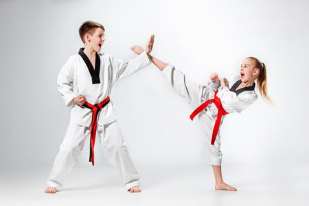 Il colpo di studio del gruppo di ragazzi che allenano le arti marziali di karate Archivio Fotografico - 75551551