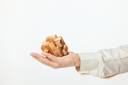 Mans hands holding wooden puzzle.