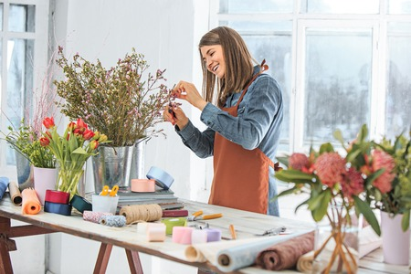 scissors: Florist at work: the young girl making fashion modern bouquet of different flowers Stock Photo