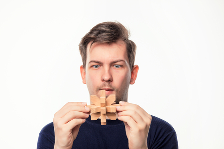 Attractive 25 year old business man looking confused at wooden puzzle. Stock Photo