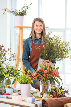 Florist at work: the young girl making fashion modern bouquet of different flowers Stock Photo