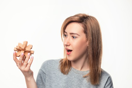 Attractive 24 year old business woman looking confused with wooden puzzle.