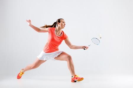 Mujer joven que juega a bádminton sobre fondo blanco Foto de archivo - 76249519