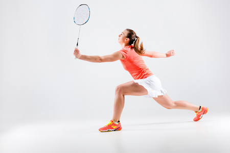 shuttlecock: Young woman playing badminton over white background