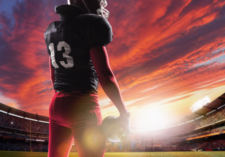 Caucasian fitness man as american football player holding a ball on stadium background at sunset