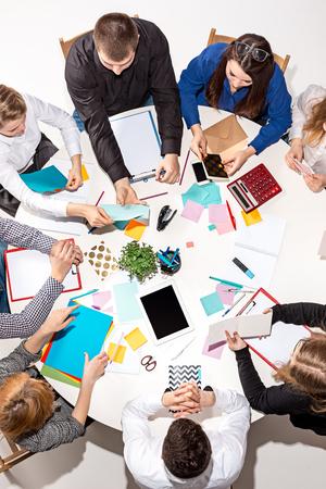 Team achter bureau zitten, rapporten controleren, praten. Bovenaanzicht Stockfoto