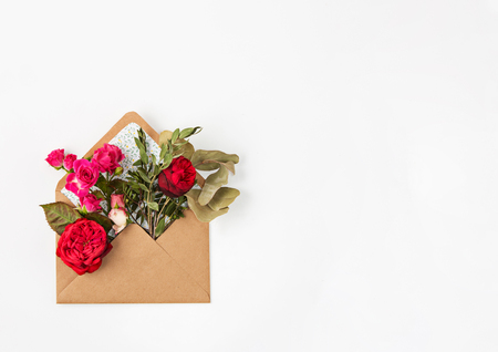 post: Love or valentines day concept. Red beautiful roses in envelopen