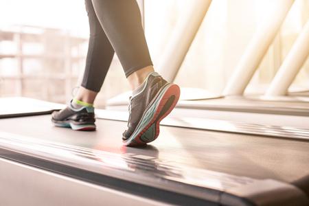 Vrouw die in een gymnastiek op een tredmolenconcept voor het uitoefenen, fitness en gezonde levensstijl loopt