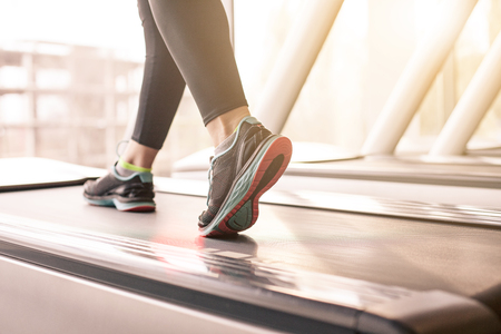 Woman running in a gym on a treadmill concept for exercising, fitness and healthy lifestyle Фото со стока