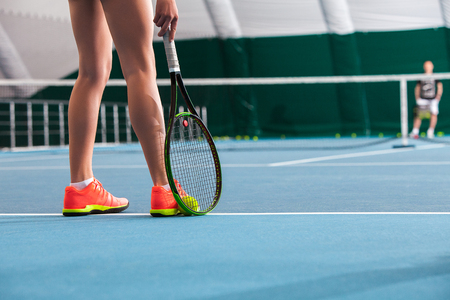 Legs of young girl in a closed tennis court with ball and racket