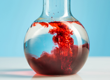 The laboratory glassware and red liquid inside on white Stock Photo