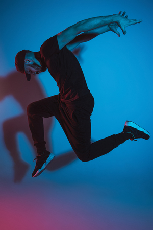 The silhouette of one hip hop male break dancer dancing on colorful background Reklamní fotografie