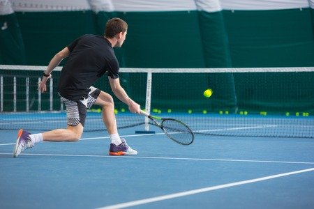 The young man in a closed tennis court with ball Stock Photo