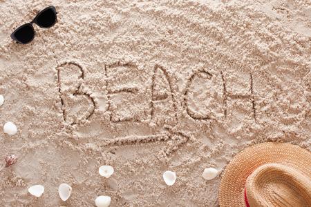 The word Beach written in a sandy tropical beach
