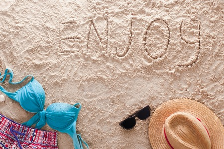 The word Enjoy written in a sandy tropical beach Stock Photo