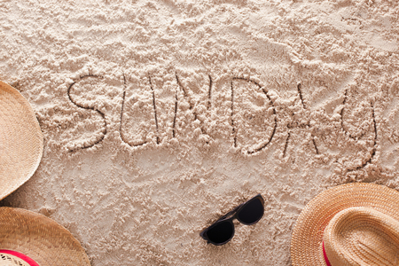 The word Sunday written in a sandy tropical beach Stock Photo