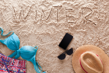 The word Winter written in a sandy tropical beach