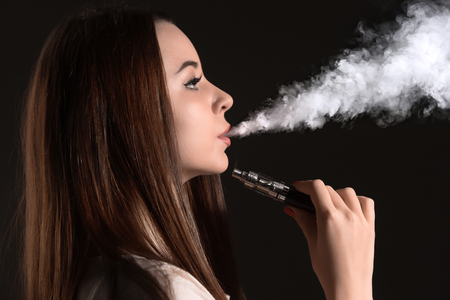 non violence: The face of vaping young woman at black studio Stock Photo