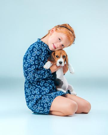 幸せな少女と灰色の背景にビーグル puppie