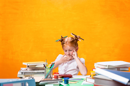 The Redhead teen girl with lot of books at home. Studio shot