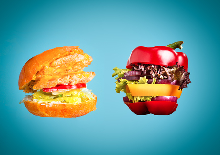 The healthy sandwich with fresh pepper, onion, salad lettuce and unhealthy harmful hamburger