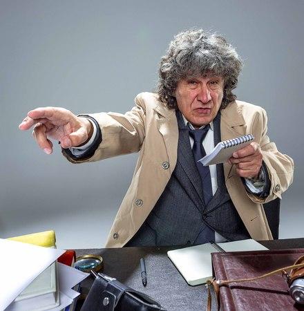 The senior man as detective or boss of mafia on gray studio background