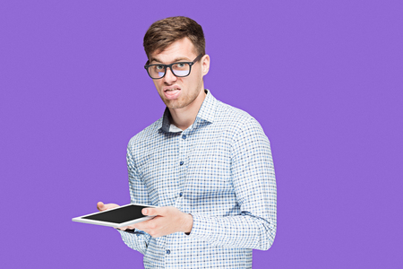 goodluck: The young man in a shirt working on laptop on lilac backgroundin Stock Photo