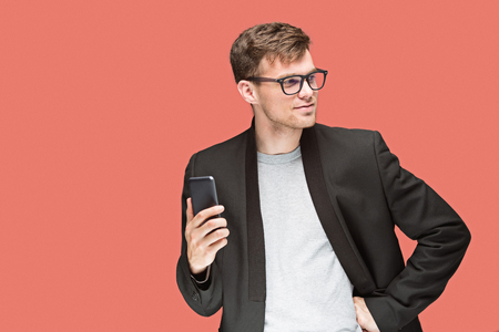 The young caucasian businessman on red background talking on cell phone Stock Photo