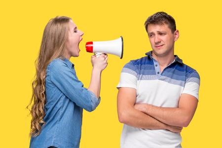 Woman shouting in megaphones at each other Stock Photo