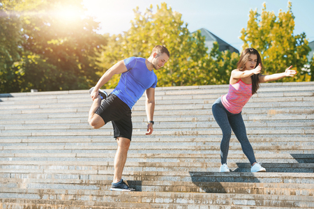 Fit fitness woman and man doing stretching exercises outdoors at park